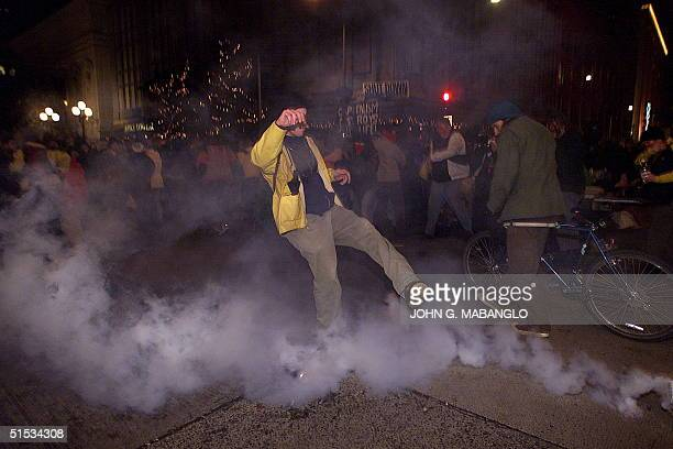 An antiWorld Trade Organization activist kicks a teargas cannister back towards Seattle Riot Police near the Washington State Convention and Trade...