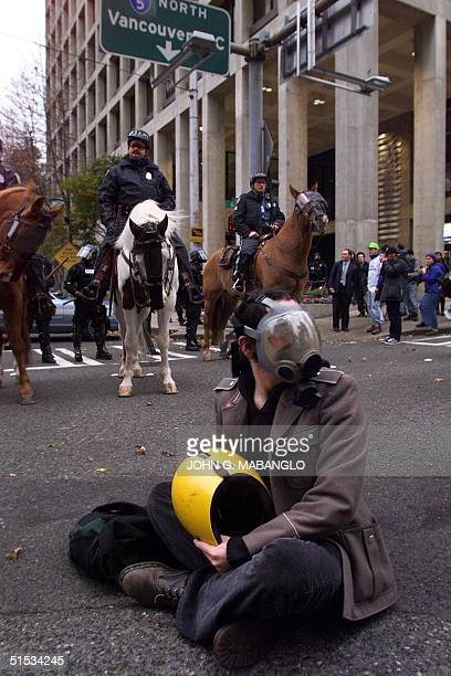 An antiWorld Trade Organization protester sits at the intersection of Sixth and Union Street in downtown Seattle Washington 29 November as mounted...