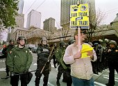An antiWTO protester holds a sign while marching by Seattle Police during a peaceful protest march 03 December 1999 in Seattle Washington Violent...