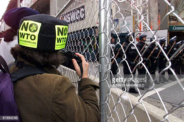 An antiWTO protester photographs Seattle riot police as they train in front of the Washington State Convention and Trade Center 29 November 1999 Tens...