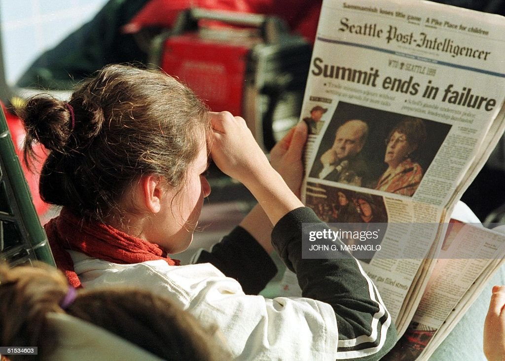 An antiWTO protester reads the day's headline featuring WTO's leading figures Director General Michael Moore and US Trade Representative Charlene...