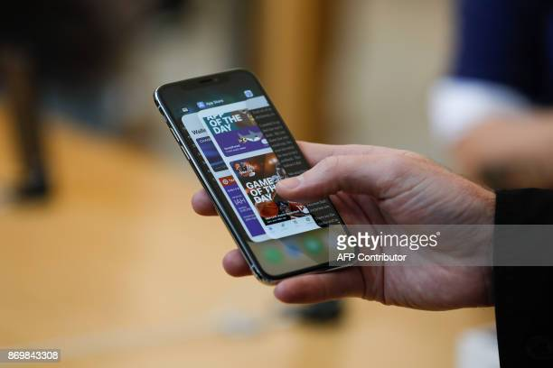 An Apple employee demonstrates the app switcher on the new iPhone X at the Apple Store Union Square on November 3 in San Francisco California Apple's...