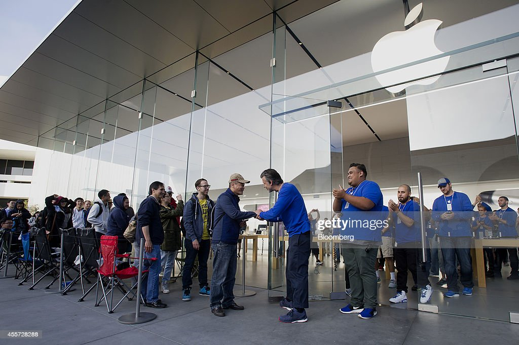 An Apple employee greets customer David Yu, who was the first in line, during the sales launch for the iPhone 6 and iPhone 6 Plus at the Apple Inc. store in Palo Alto, California, U.S., on Friday, Sept. 19, 2014. Apple Inc.'s stores attracted long lines of shoppers for the debut of the latest iPhones, indicating healthy demand for the bigger-screen smartphones. The larger iPhone 6 Plus is already selling out at some stores across the U.S. Photographer: David Paul Morris/Bloomberg via Getty Images