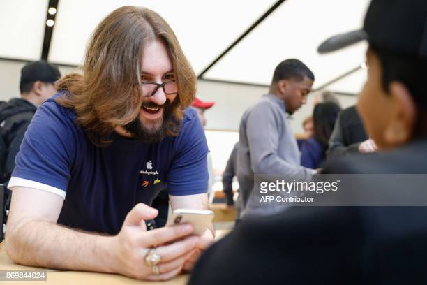 An Apple employee holds the new iPhone X while speaking to as young boy at the Apple Store Union Square on November 3 in San Francisco California...