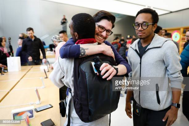 An Apple employee hugs a customer after selling him a new iPhone X at the Apple Store Union Square on November 3 in San Francisco California Apple's...