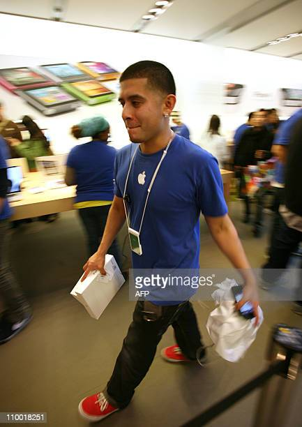 An Apple employee runs around to help out customers who came to Apple Store in downtown San Francisco to purchase the second generation iPad iPad 2...