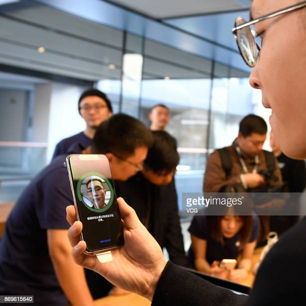 An Apple fan tries the newly released iPhone X at the Sanlitun Apple Store on November 3 2017 in Beijing China iPhone X go on sale on Friday and...