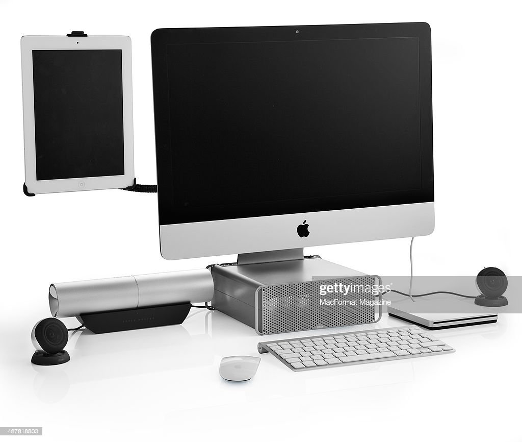 An Apple IMac photographed on a white background with a selection of Apple-compatible accessories and hardware, including an iPad HoverBar, Twelve South HiRise stand, Edifier Aurora speakers and USB SuperDrive, taken on August 9, 2013.