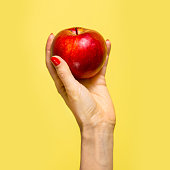 An apple in a hand over yellow background