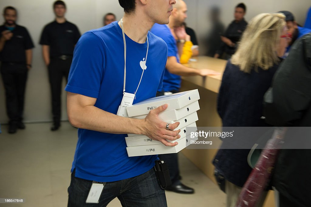 An Apple Inc. employee carries a stack of new iPad Air devices on the first day of sales at the 5th Avenue Apple store in New York, U.S., on Friday, Nov. 1, 2013. Apple Inc.'s forecast for the slowest holiday sales growth in a half decade reflects how iPhones and iPads aren't providing the growth surges they once did as competition accelerates in the saturated mobile market. Photographer: Craig Warga/Bloomberg via Getty Images