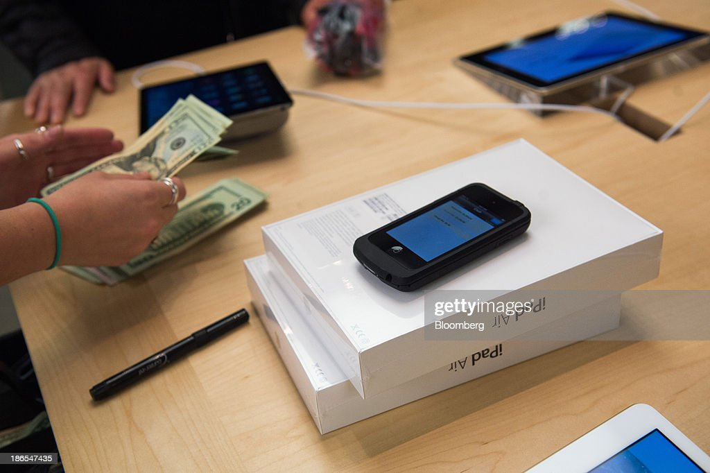 An Apple Inc. employee counts cash while helping a shopper purchase the new iPad Air at the 5th Avenue Apple store in New York, U.S., on Friday, Nov. 1, 2013. Apple Inc.'s forecast for the slowest holiday sales growth in a half decade reflects how iPhones and iPads aren't providing the growth surges they once did as competition accelerates in the saturated mobile market. Photographer: Craig Warga/Bloomberg via Getty Images