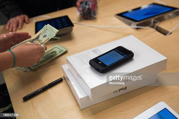 An Apple Inc employee counts cash while helping a shopper purchase the new iPad Air at the 5th Avenue Apple store in New York US on Friday Nov 1 2013...