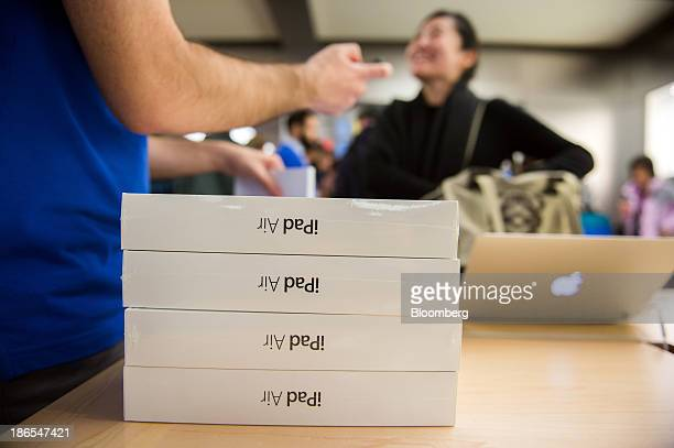 An Apple Inc employee helps a shopper purchase the new iPad Air at the 5th Avenue Apple store in New York US on Friday Nov 1 2013 Apple Inc's...