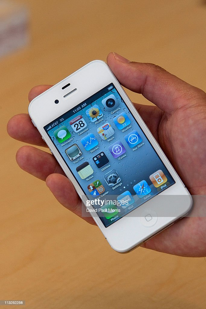 An Apple Inc., employee holds the new white iPhone 4 at the Apple store April 28, 2011 in Palo Alto, California. The long awaited white iPhone, first announced in June of 2010, went on sale worldwide for the first time today.