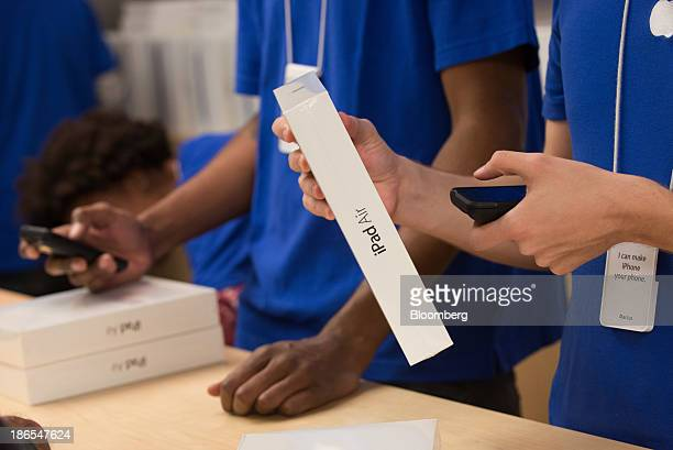 An Apple Inc employee scans the price of a new iPad Air on the first day of sales at the 5th Avenue Apple store in New York US on Friday Nov 1 2013...