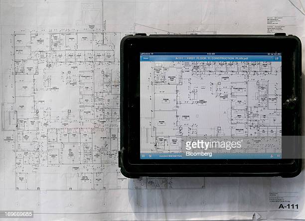 An Apple Inc iPad displays Autodesk Inc architectural drawings next to paper blueprints in this arranged photo at a Skanska USA Building Inc Inova...