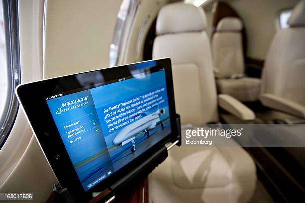 An Apple Inc iPad displays information inside the cabin of a new Netjets Inc Embraer Phenom 300 jet in the Signature Fight Services hangar at Eppley...