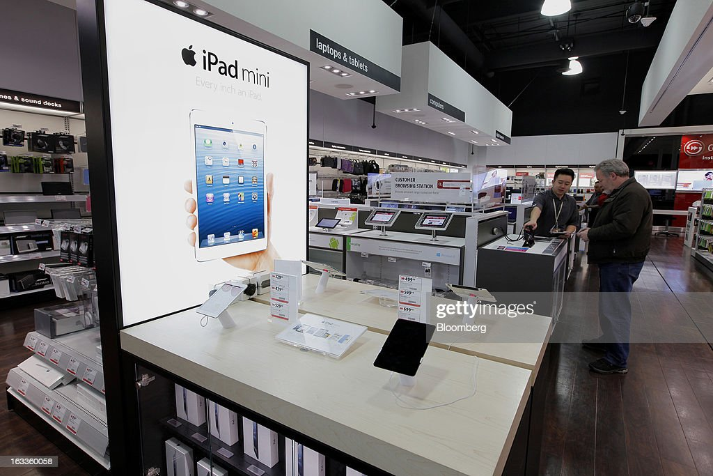 An Apple Inc. iPad Mini display is seen as employee Tim Dang, left, assists a customer at a Future Shop store in Vancouver, British Columbia, Canada, on Thursday, March 7, 2013. Future Shop, Canada's largest consumer electronics retailer, offers home and entertainment products, including televisions, computers, cameras, MP3 players, video games, computer add-ons, software, and audo and video systems. Photographer: Deddeda White/Bloomberg via Getty Images