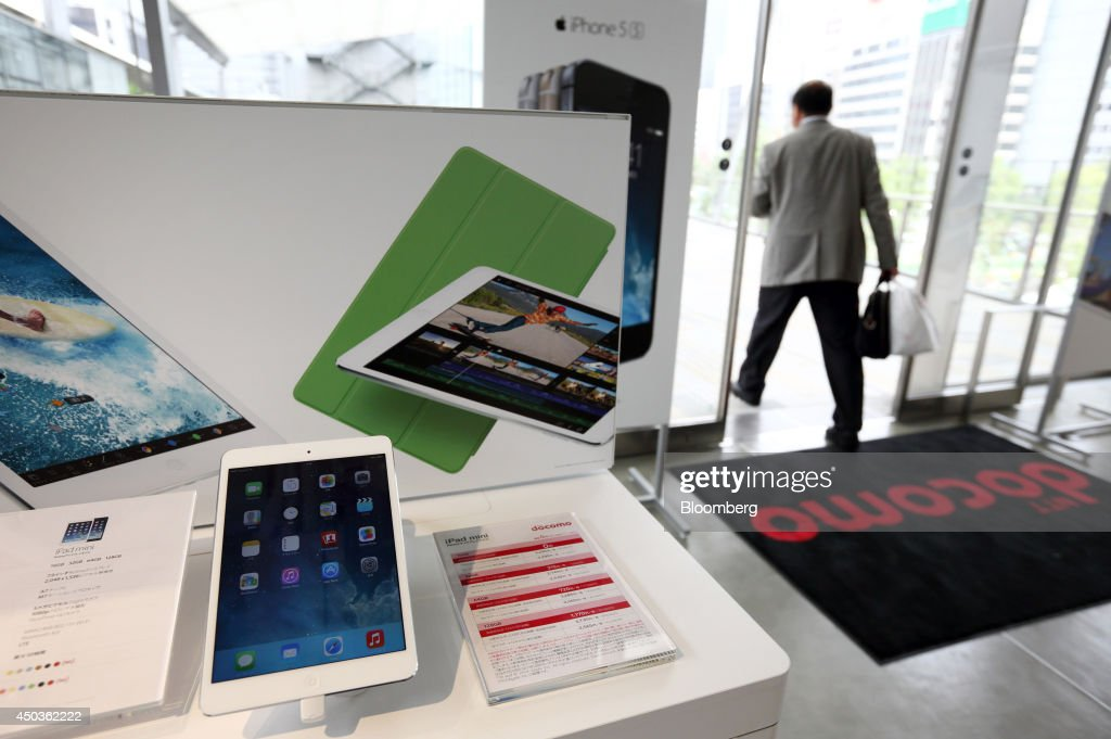 An Apple Inc. iPad mini is displayed while a customer exits an NTT Docomo Inc. store in Tokyo, Japan, on Tuesday, June 10, 2014. NTT Docomo, Japan's largest wireless carrier by subscribers, began offering Apple Inc's iPad today. Photographer: Tomohiro Ohsumi/Bloomberg via Getty Images
