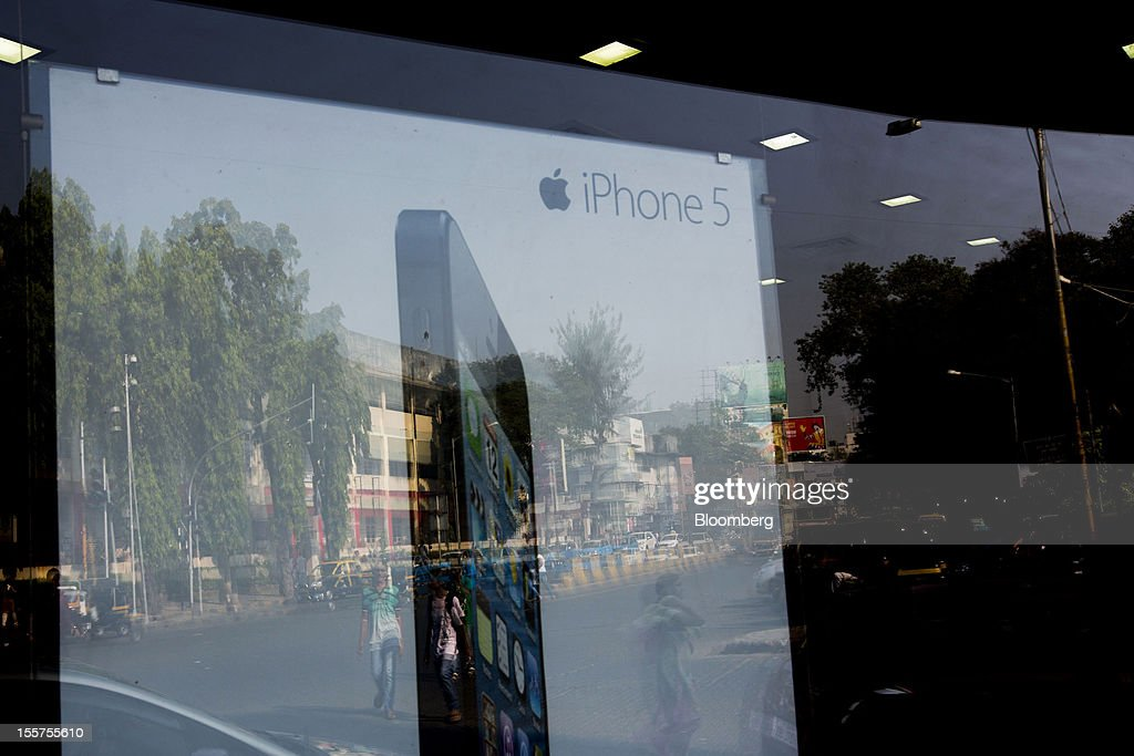 An Apple Inc. iPhone 5 advertisement stands in Mumbai, India, on Tuesday, Nov. 6, 2012. Reserve Bank of India Governor Duvvuri Subbarao lowered the RBI's forecast for India's gross domestic product growth in the year through March to 5.8 percent, the slowest in almost a decade, from 6.5 percent. Photographer: Brent Lewin/Bloomberg via Getty Images