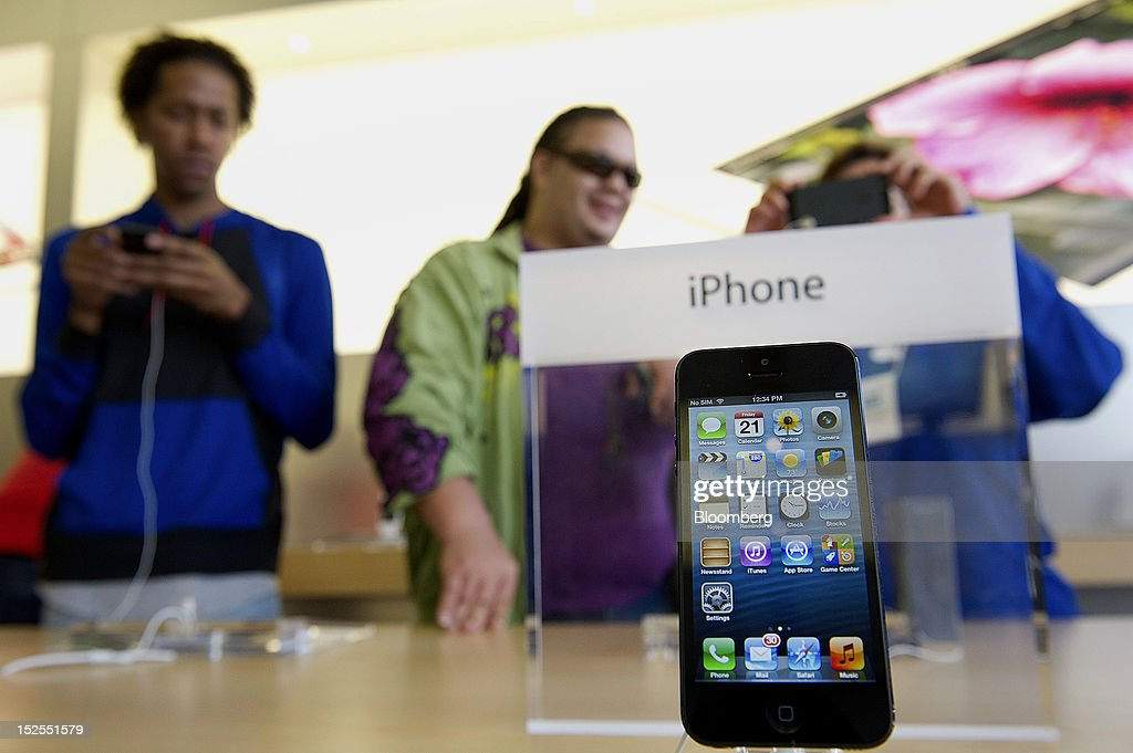 An Apple Inc. iPhone 5 is displayed while customer look over devices at a store in San Francisco, California, U.S., on Friday, Sept. 21, 2012. Apple Inc. is poised for a record iPhone 5 debut and may not be able to keep up with demand as customers lined up in Sydney, Tokyo, Paris and New York to pick up the latest model of its top-selling product. Photographer: David Paul Morris/Bloomberg via Getty Images