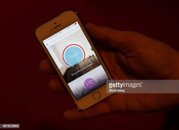 An Apple Inc iPhone displays a smart air purifier mobile application manufactured by Royal Philips NV in this arranged photograph during the...