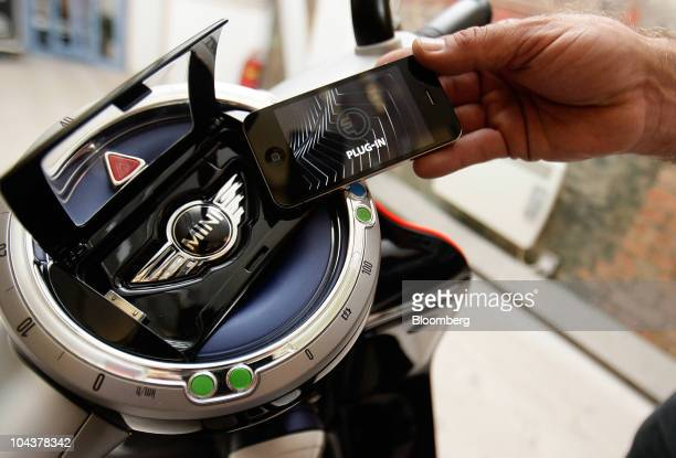 An Apple Inc iPhone is placed into a docking station on the new Mini Scooter E Concept by Bayerische Motoren Werke AG at its launch in London UK on...