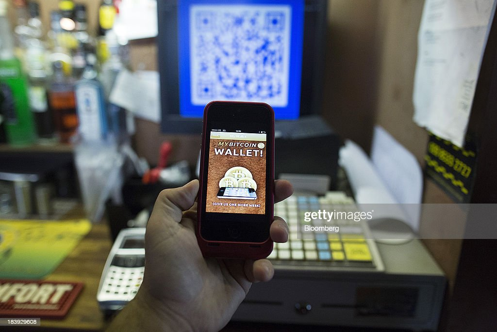 An Apple Inc. iPhone5 displays the Bitcoin smartphone app in this arranged photograph at the bar of the Pembury Tavern in London, U.K., on Wednesday, Oct. 9, 2013. Bitcoins are being adopted by a few merchants, enabling customers to buy beer at Pembury Tavern in East London, cocktails at EVR bar in New York and dessert at Cups and Cakes Bakery in San Francisco. Photographer: Simon Dawson/Bloomberg via Getty Images