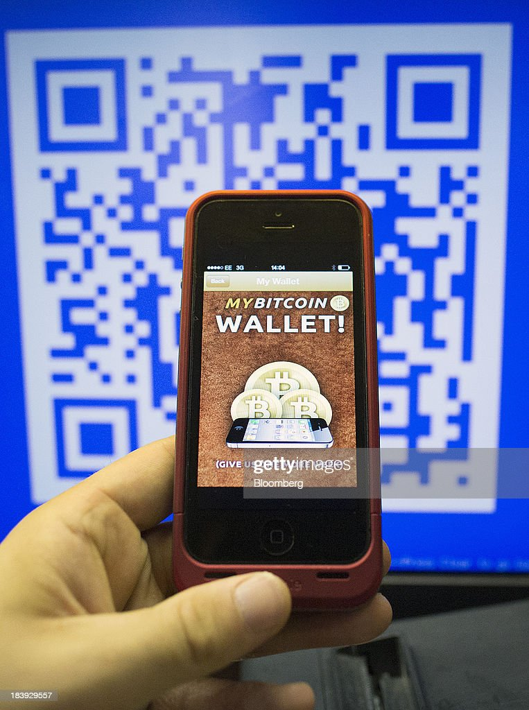 An Apple Inc. iPhone5 displays the Bitcoin Wallet smartphone app as a quick response (QR) code is displayed on the monitor of a cash register in this arranged photograph at the Pembury Tavern in London, U.K., on Wednesday, Oct. 9, 2013. Bitcoins are being adopted by a few merchants, enabling customers to buy beer at Pembury Tavern in East London, cocktails at EVR bar in New York and dessert at Cups and Cakes Bakery in San Francisco. Photographer: Simon Dawson/Bloomberg via Getty Images