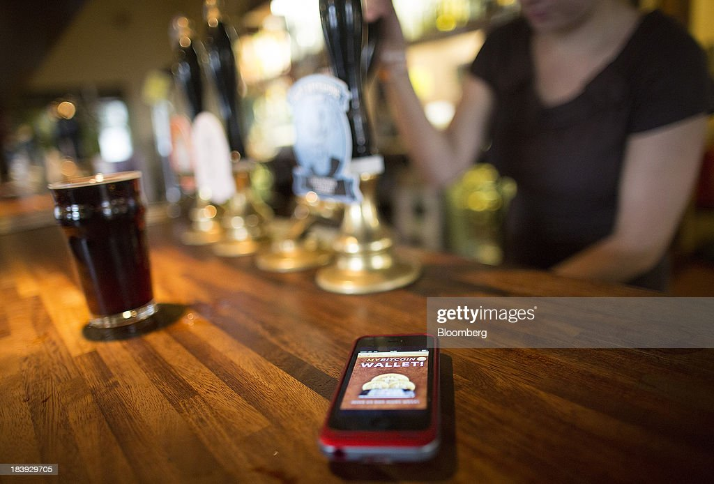 An Apple Inc. iPhone5 displays the Bitcoin Wallet smartphone app as a bar worker pours a pint of beer of the Pembury Tavern in this arranged photograph in London, U.K., on Wednesday, Oct. 9, 2013. Bitcoins are being adopted by a few merchants, enabling customers to buy beer at Pembury Tavern in East London, cocktails at EVR bar in New York and dessert at Cups and Cakes Bakery in San Francisco. Photographer: Simon Dawson/Bloomberg via Getty Images