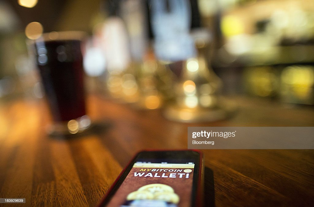 An Apple Inc. iPhone5 displays the Bitcoin Wallet smartphone app as it sits on the bar of the Pembury Tavern in this arranged photograph in London, U.K., on Wednesday, Oct. 9, 2013. Bitcoins are being adopted by a few merchants, enabling customers to buy beer at Pembury Tavern in East London, cocktails at EVR bar in New York and dessert at Cups and Cakes Bakery in San Francisco. Photographer: Simon Dawson/Bloomberg via Getty Images
