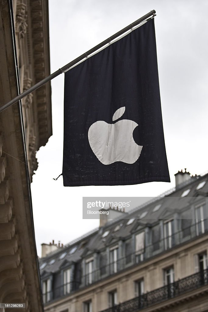 An Apple Inc. logo sits on a flag hanging outside the company's computer store in Paris, France, on Thursday, Sept. 19, 2013. Bank of France General Council member Bernard Maris said France will end up restructuring its debt as tax 'optimization' by large companies including Google Inc. will leave too big a burden on the middle class. Photographer: Balint Porneczi/Bloomberg via Getty Images