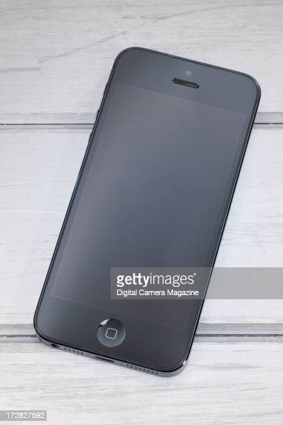 An Apple iPhone 5 photographed on a wooden background taken on November 13 2012
