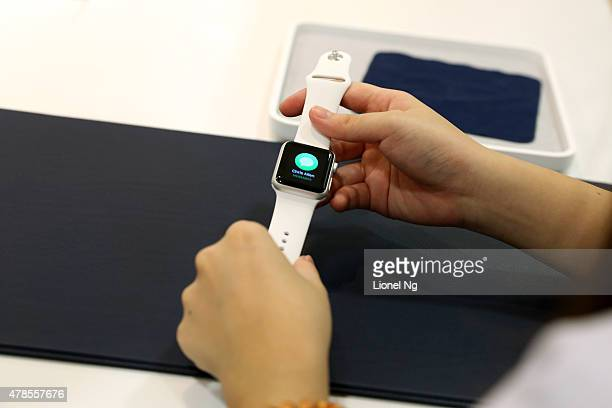 An Apple retail store employee holds an Apple Watch during the first day of the Apple Watch offical launch on June 26 2015 in Singapore