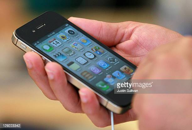 An Apple Store customer looks at the new Apple iPhone 4Gs on October 14 2011 in San Francisco United States The new iPhone 4Gs went on sale today and...