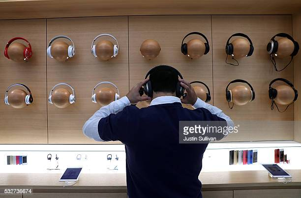 An Apple Store employee tries on a pair of headphones during a press preview of the new flagship Apple Store on May 19 2016 in San Francisco...