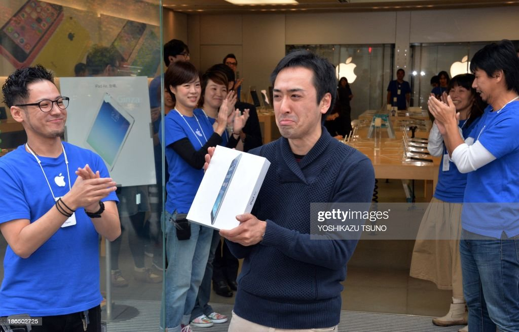 An Apple store's first customer of the day (C) displays a package containing Apple's new 'iPad Air' tablet at in Tokyo on November 1, 2013. Over 300 customers queued up for the new slim iPad Air as the tablet launched worldwide. AFP PHOTO / Yoshikazu TSUNO