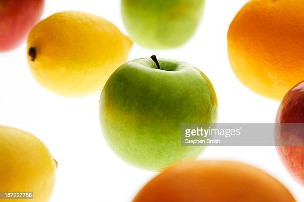 An apple, surrounded by oranges and lemons