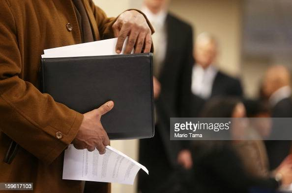 An applicant goes through paperwork at a Manhattan job fair on January 17 2013 in New York City Weekly jobless claims fell to a five year low with...