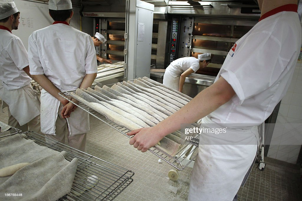 An apprentice carries breads dough to the oven at the National Bakery and Pastry Institute (INBP - Institut National de Boulangerie et de Patisserie) on November 20, 2012 in the northwestern city of Rouen. AFP PHOTO/CHARLY TRIBALLEAU