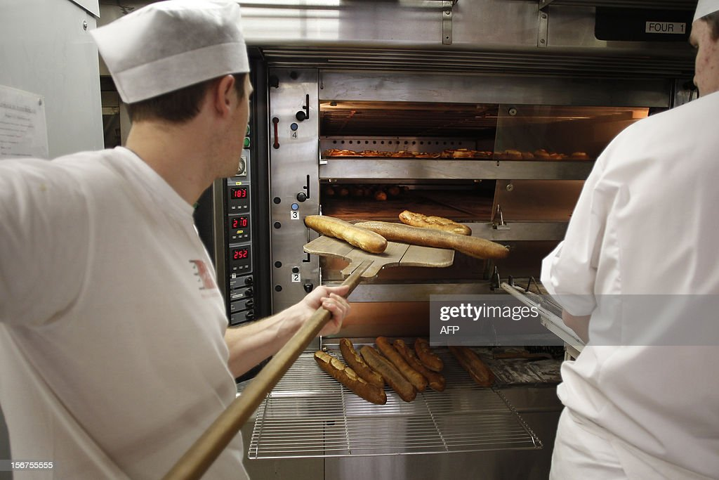 An apprentice removes bread from the oven at the National Bakery and Pastry Institute (INBP - Institut National de Boulangerie et de Patisserie) on November 20, 2012 in the northwestern city of Rouen.