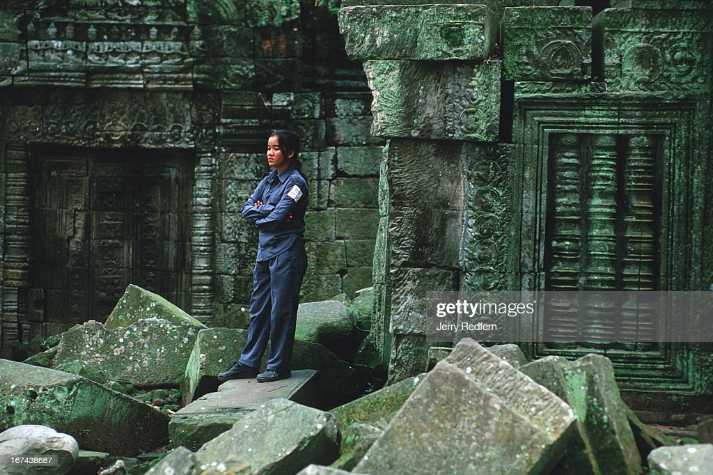 An Apsara Authority guard spends a quiet moment amid the ruins of Ta Prohm temple in the Angkor complex. The Apsara Authority is in charge of preserving and protecting the Angkor ruins..