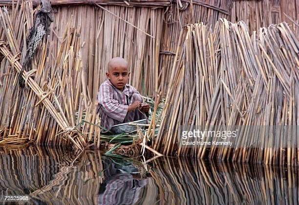 An Arab child sits by his house in a marsh near Basra 1990 in southern Iraq
