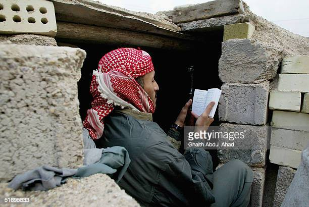 An Arab fighter reads the Quraan outside his bunker as US airplanes bomb the city on November 7 2004 in the city of Fallujah Iraq The Mujahadeen are...