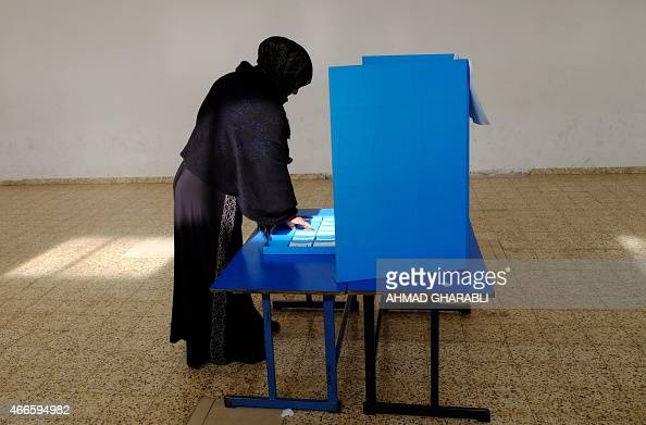 An Arab Israeli woman prepares to cast her ballot at a polling station in the northern Israeli town of Umm alFahm on March 17 2015 Voting polls...