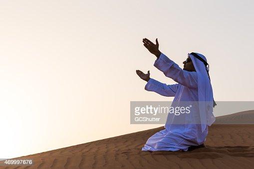 An Arab man praying in desert, Dubai