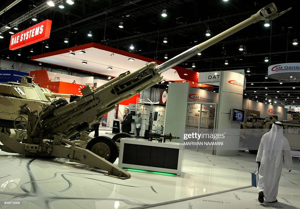 An Arab man walks past an M777 A2 lightweight 155mm Howitzer on the opening day of the International Defence Exhibition and Conference in Abu Dhabi...