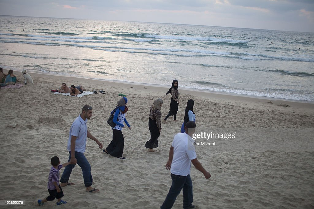 An Arab Muslim Israeli family walks on the beach on the first day of Eid al-Fitr on July 28, 2014 in Tel Aviv, Israel. As Israel's operation 'Protective Edge' in Gaza continues, the international community struggles to find a truce agreement.