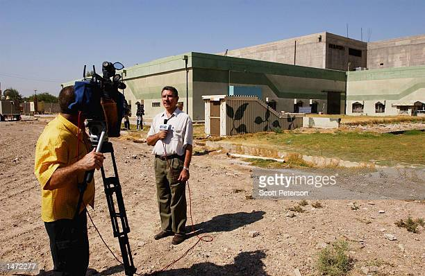 An Arab TV journalist stands in front of the Al Furat military facility that Iraq officials say is no longer used for their nuclear program October...