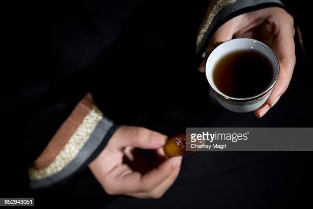 An arab woman holding a bowl of dates and gawa (Arabian Coffee).